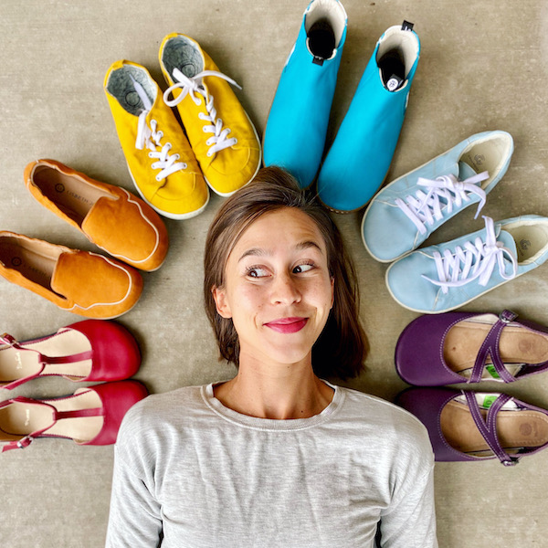 A top down view of a woman's face smilind surrounded by a rainbow of colorful barefoot shoes